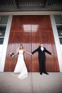 Bride and Groom standing in front of a big wooden door
